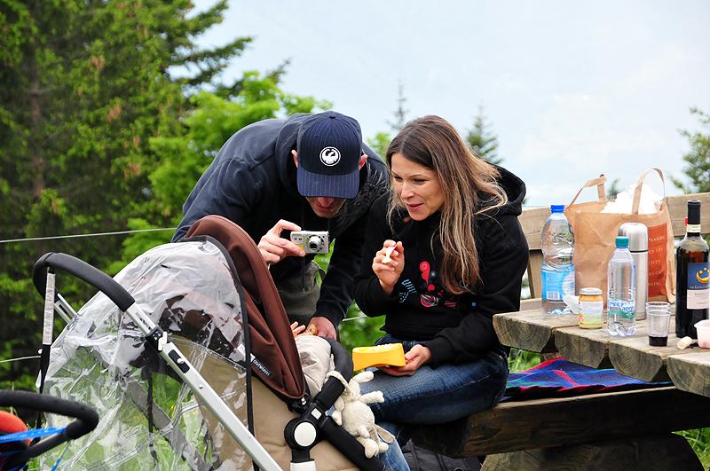 Couple admirant et photographiant leur bebe dans une poussette