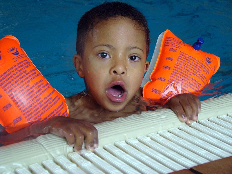 Jeune garçon dans une piscine se tenat au bord de celle-çi
