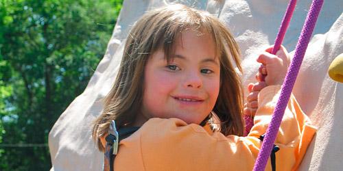 Une fillette accrochée à une corde rose lors d'une initiation à l'escalade.