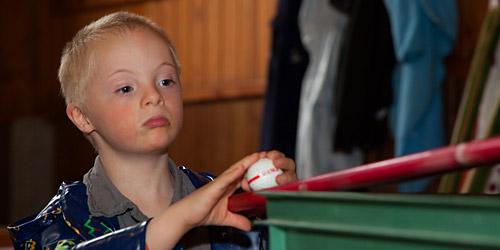 Un jeune garçon, intéressé et attentif, observe une table de billard.