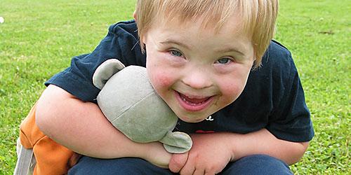 un petit garçon accroupi dans l'herbe avec son doudou