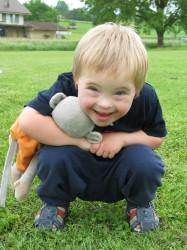 un jeune garçon curieux accroupi, son singe-doudou sous le bras