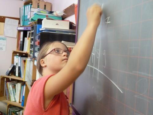 une fillette fait un calcul au tableau noir