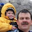 un papa portant son jeune garçon sur le dos
